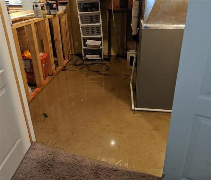 furnace room floor with water on it, and furnace