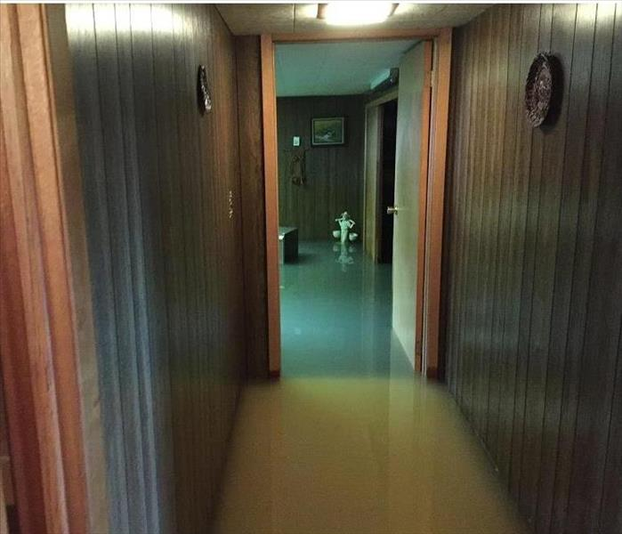 hallway with over 1 foot of water and panel walls