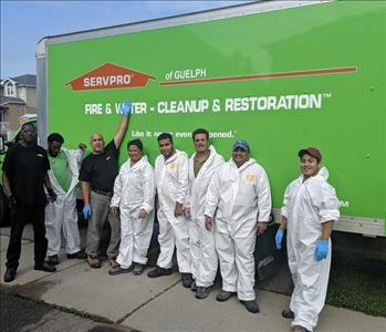 8 people standing against a SERVPRO vehicle
