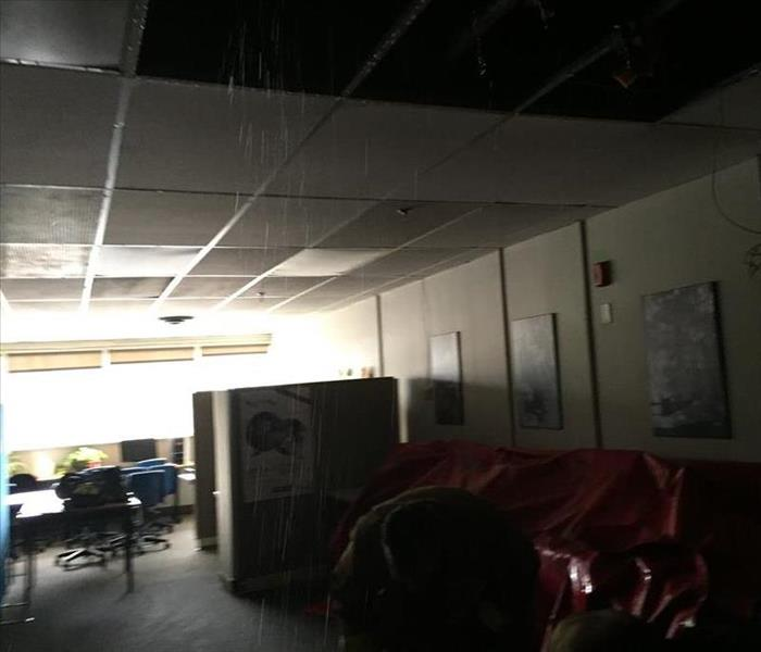 Water dripping down on ceiling tiles in this office