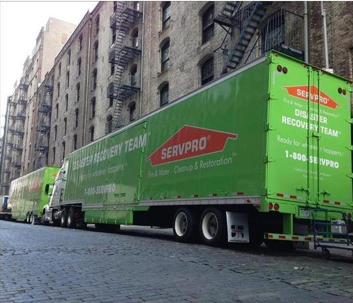 Apartment complex with two SERVPRO transport trucks parked in front