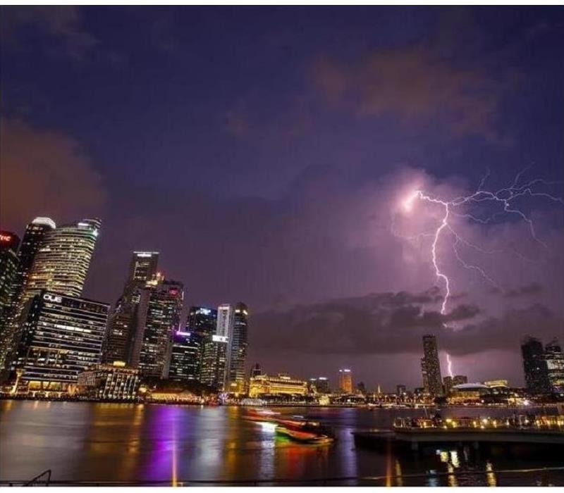 a city skyline with a lightning bolt in the background